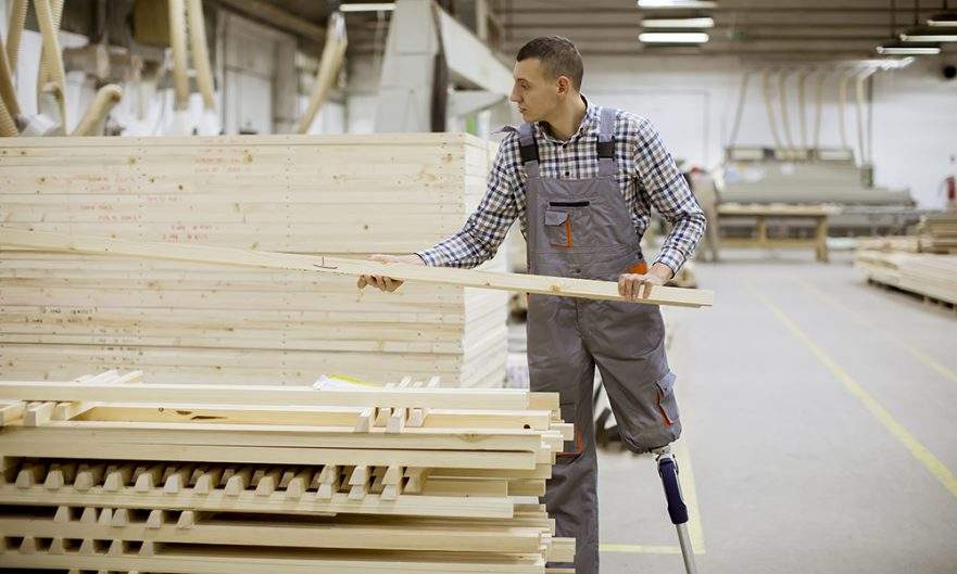 A man with a prosthetic leg lifts a large board from a pile in a lumber mill.