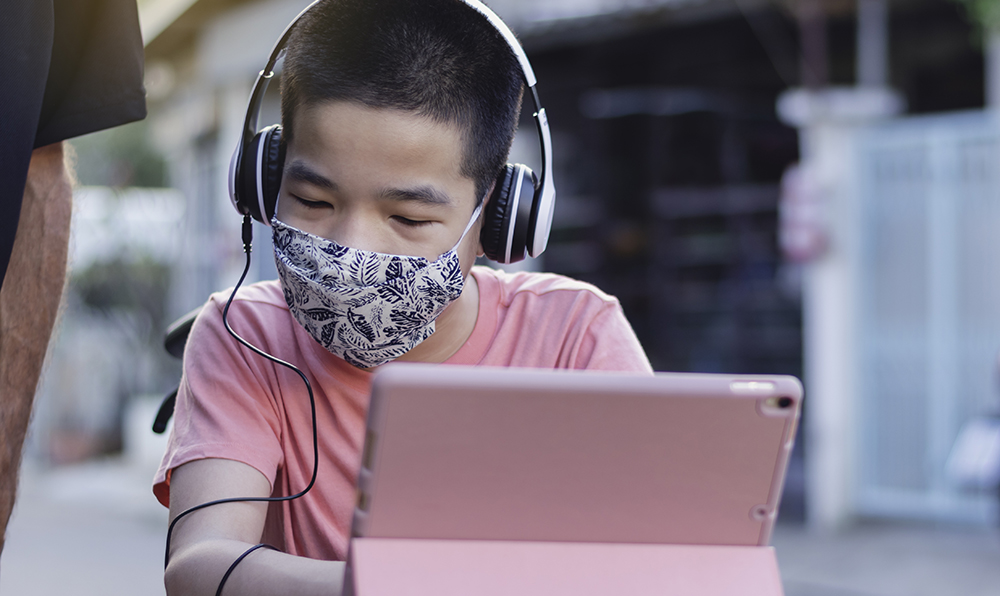 A little boy wears a COVID mask and sits in front of a tablet.