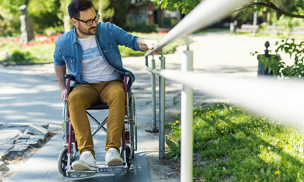 A young man in a wheelchair uses a handrail to go up a ramp.