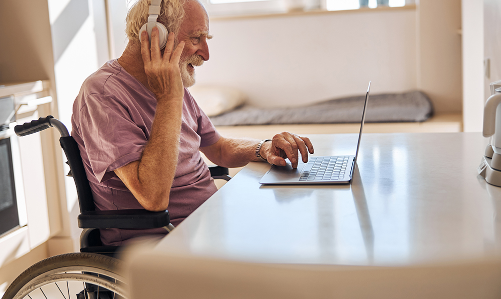 An elderly man in a wheelchair sits in an apartment in front of a laptop wearing headphones and smiling