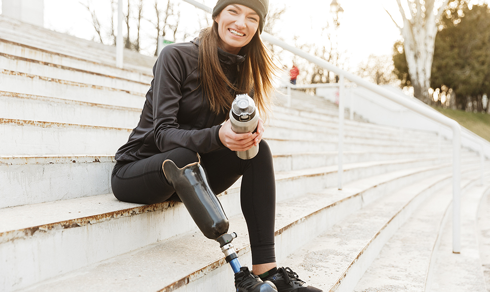 A stylish woman sits on concrete bleachers. She is wearing athletic gear, has a water bottle, a big smile and a prosthetic leg.