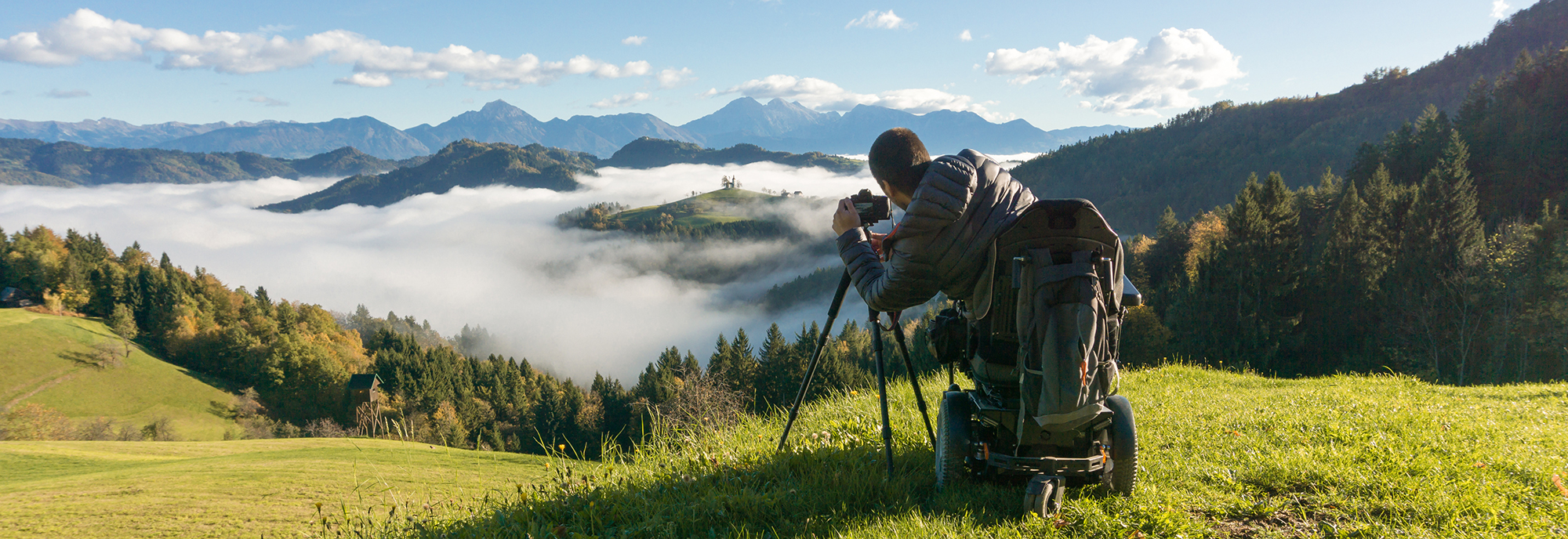 A man in a power wheelchair sits at the top of a mountain overlooking forest and other mountains covered in mist. He is using a professional camera to photograph the scene.