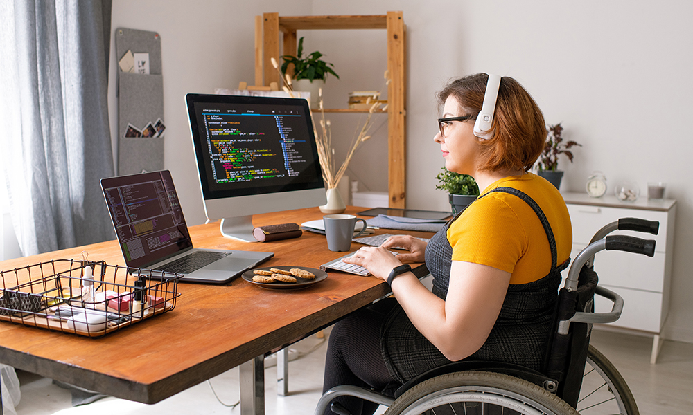 A young woman sits at a desk in her home. She is in a wheelchair in front of a computer with an additional screen, she is coding something.