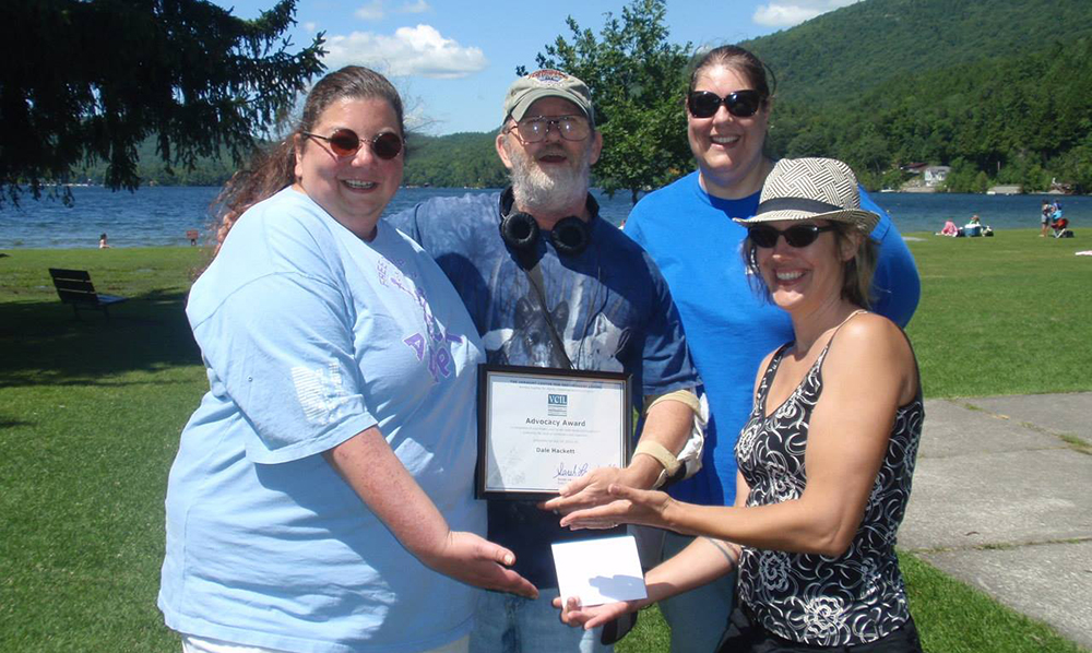 A group of VCIL staff stands in front of a pond on a sunny day, they're holding an award and all smiling.