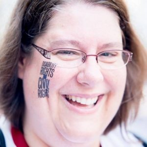 A very close up photo of Sarah Launderville. She has a big bright smile and writing on her face that says 'Disability Rights are Civil Rights.'