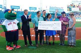 A group stands on the Red Sox baseball field presenting an oversized check to VCIL.