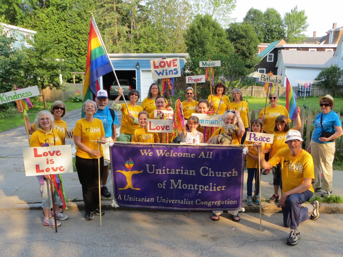 A group of people from the Unitarian Church are gathered together with flags and rainbows and a large banner about their church.