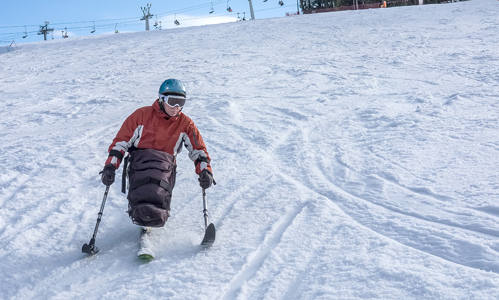 A man is sit-skiing down a mountain at a ski resort.