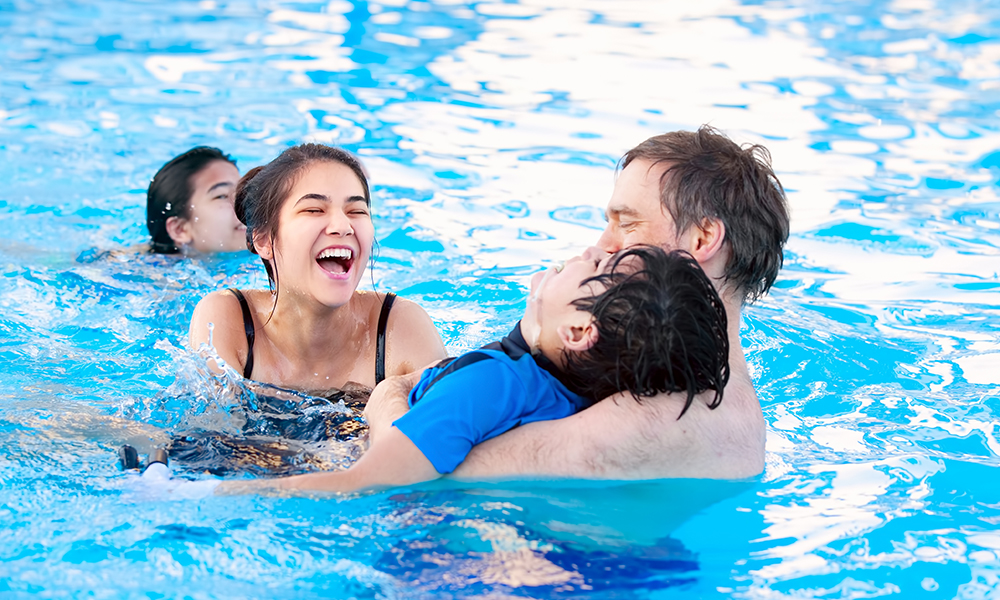 A family is swimming in an indoor pool. The son has a physical disability and the dad is holding him in the water while they all laugh.