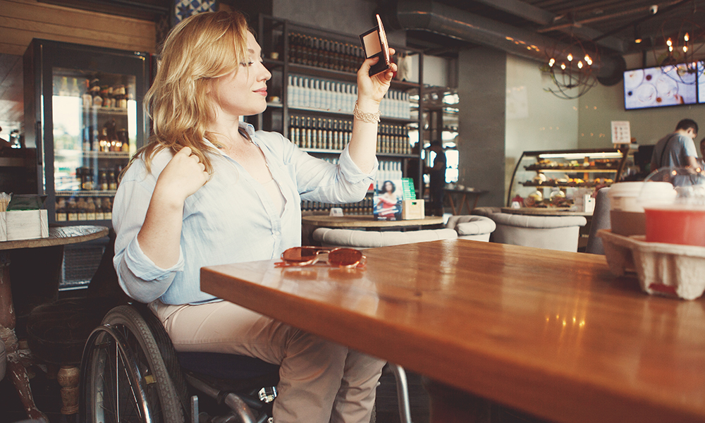 A pretty teenage girl sits in her wheelchair at a cafe. She is taking a selfie with her phone.