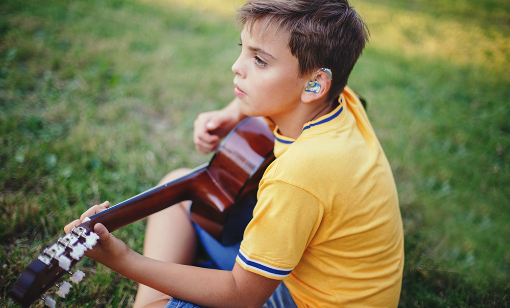 A young boy is sitting with his back slightly to the camera. He has a hearing aid and is playing the guitar.