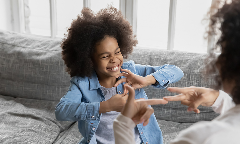 The camera looks over an adults shoulder who is using ASL with a small girl. She has a huge smile and a head full of curls