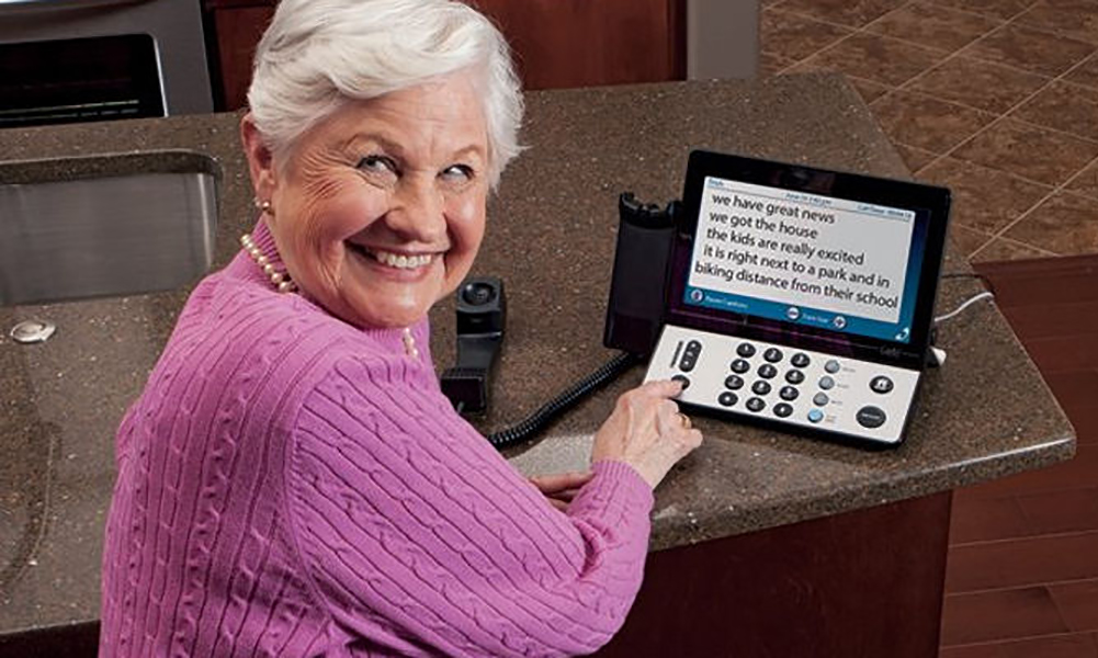 A smiling elderly woman in a pink sweater turns towards the camera from her caption phone