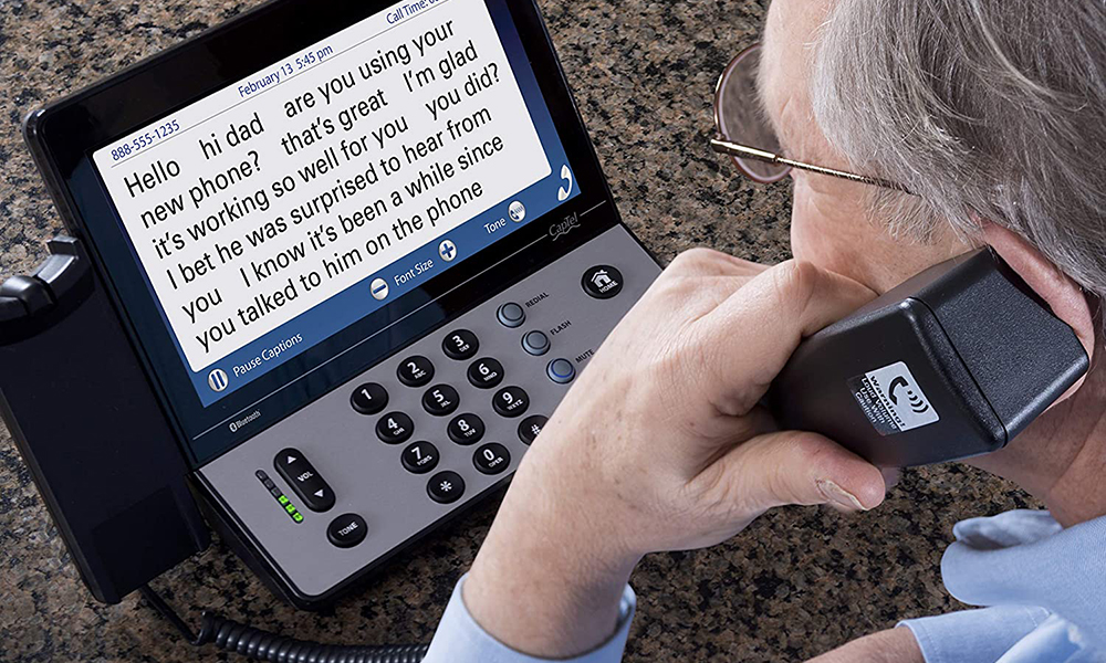 A close-up of a captioning phone while an elderly man uses it