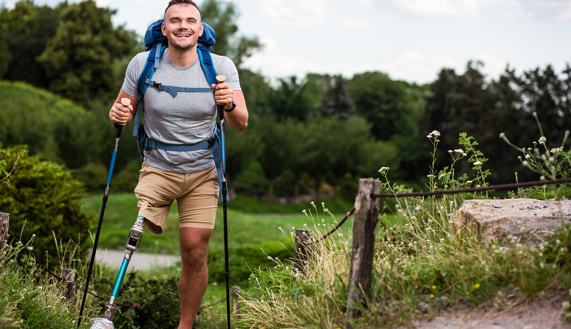 A young man with a prosthetic leg is on a hiking trail. He has a big backpack, two hiking sticks and a very happy smile.