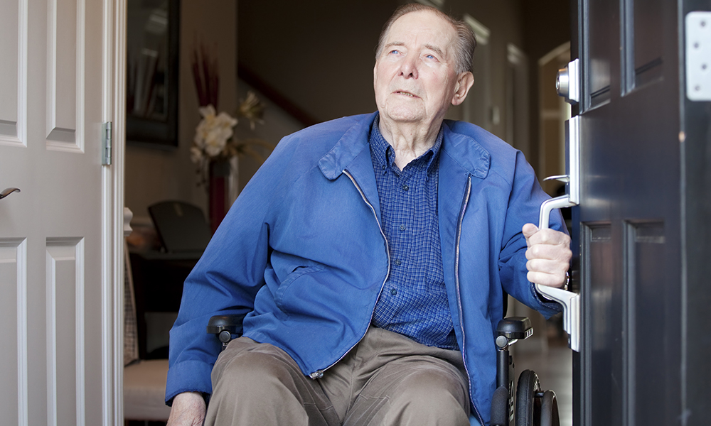 An older man in a power chair wearing a blue jacket is exiting his front door.