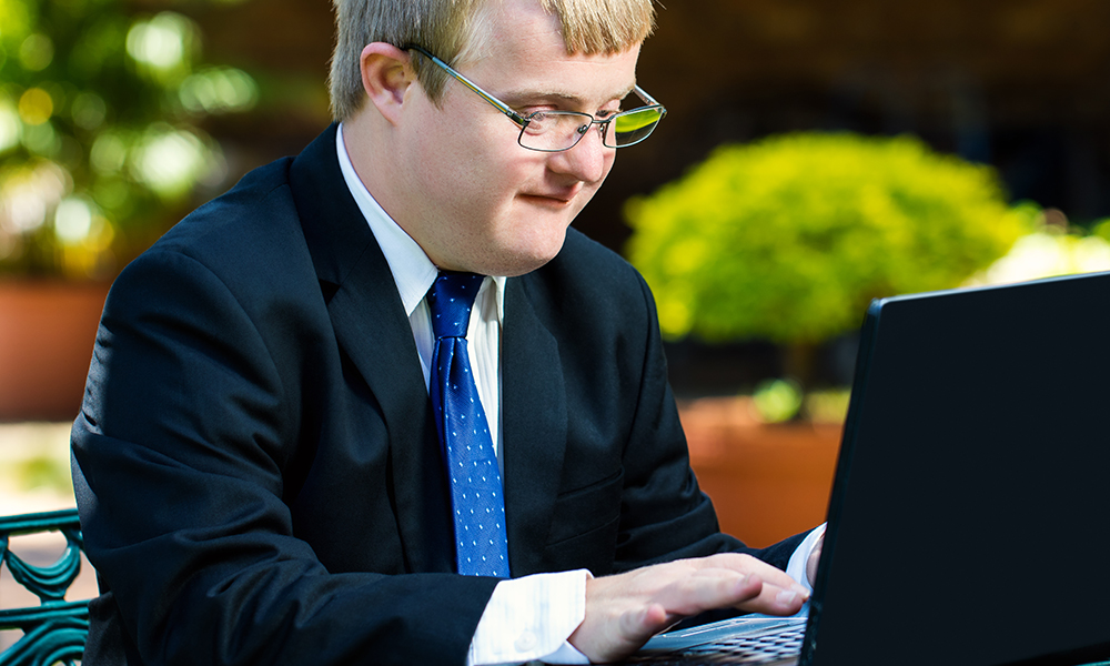 A young adult man is wearing a suit and blue tie. He has Downs Sydrome and is sitting at a laptop very focused.