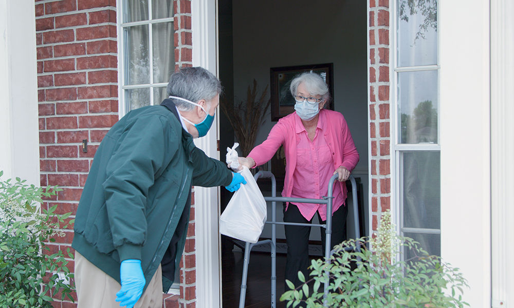 An older man is delivering a meal to an elderly woman at her front door.