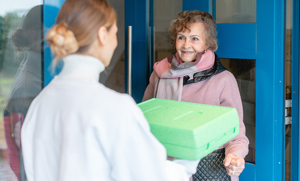 A young girl is handing a large green box to an elderly woman at her front door