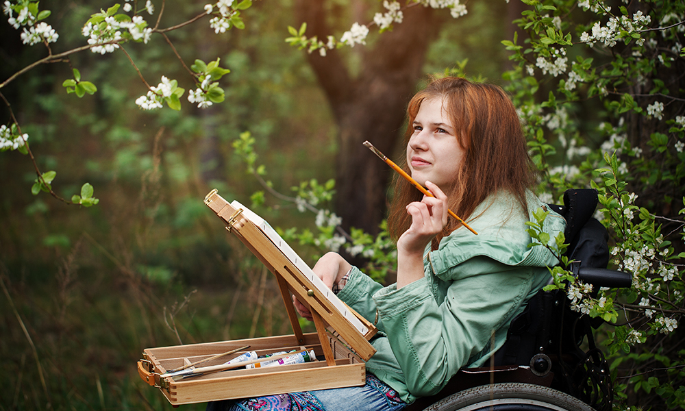 A young redheaded woman in a power chair sits amongst flowering trees with a painting palette and brush