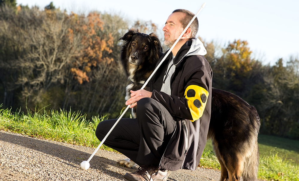 A man who is blind is kneeling down besides his guide dog. The dog is large and black and looks towards the camera