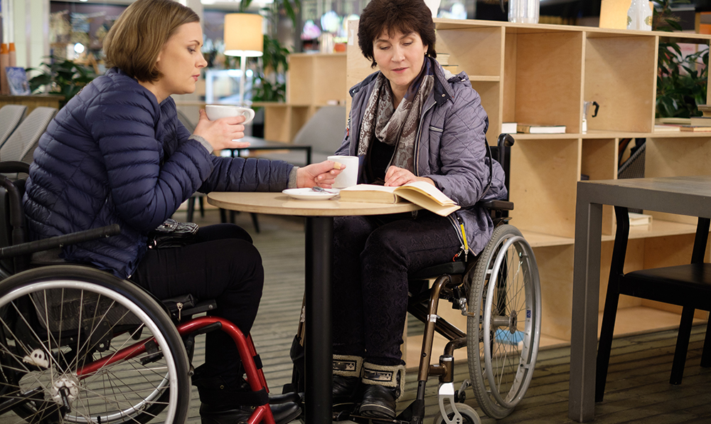 Two women in wheelchairs sit around a small table in a bookstore, both looking at the same book