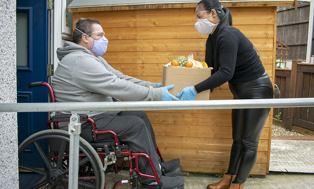 A man in a wheelchair wearing grey sweats is at his front door receiving a box of groceries from a woman
