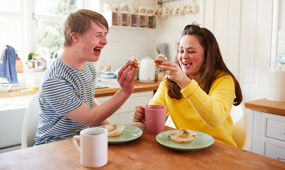 A young adult couple with Downs Syndrome are laughing in a bright cheery kitchen, they are have a 'cheers' with cupcakes