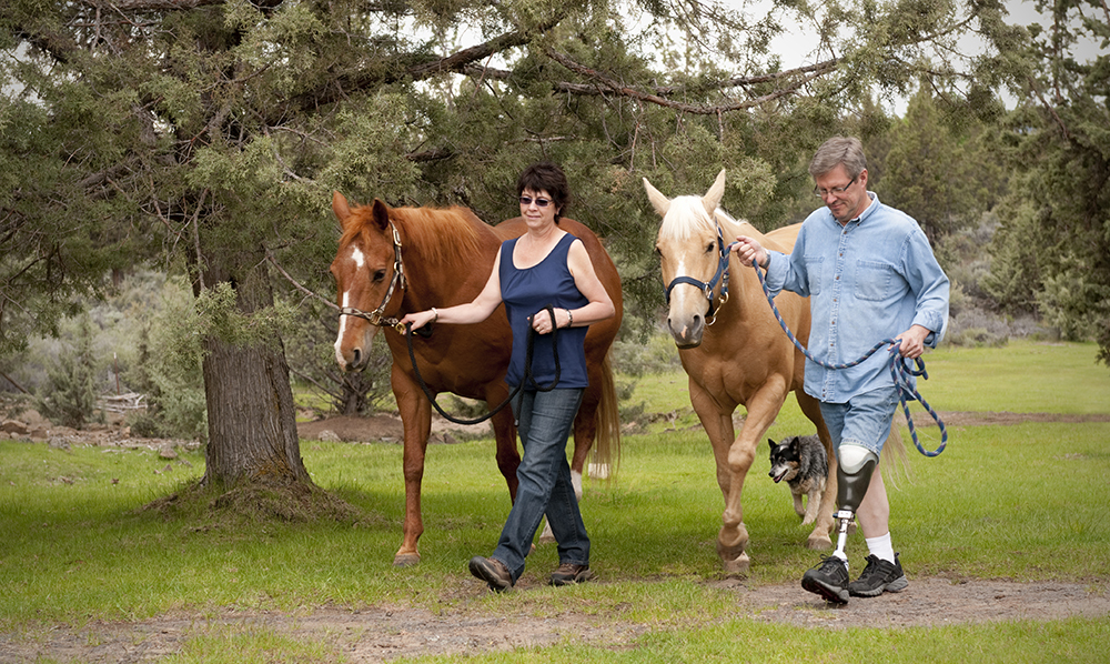 A middle aged man with a prosthetic leg and a woman walk two horses through a tree lined path.