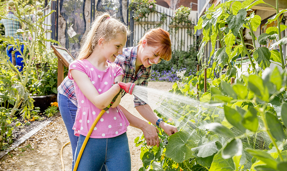 A young female child with a limb difference is smiling in a big garden while using a hose to water the plants.