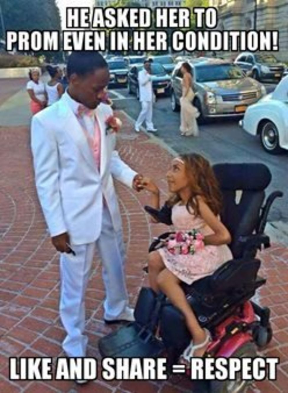 """A young man in a white tux stands with a young woman in a prom dress in a wheelchair. There are other going to prom behind them. The photo says """"He asked her to prom even in her condition! Like and share = Respect"""""""